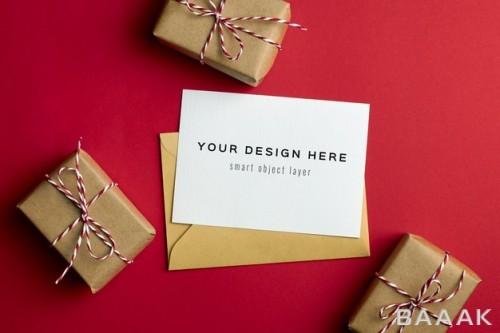 موکاپ کارت تبریک با جعبه های هدایا و بکگراند قرمز کاغذی
