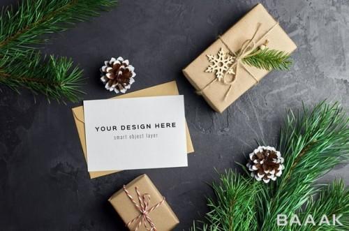 موکاپ کارت تبریک با هدایای کریسمس و شاخه های درخت کاج